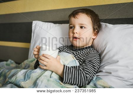 Sick Cute Curing Boy Lying On Bed On Pillow Under Blanket Taking Medicament In Cup