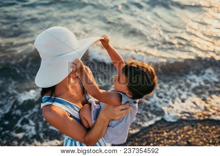 Cute Top View Of Young Mother Playing With Daughter With White Hat At The Sea Background. Family Vac