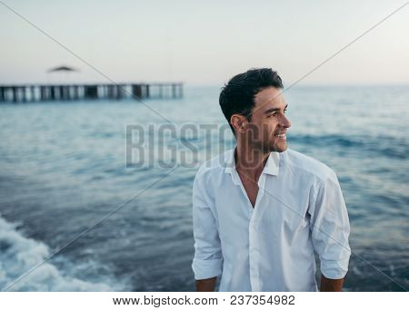 Handsome Happy Man Wearing White Shirt At The Sea Or The Ocean Background. Travel Vacation Holiday.