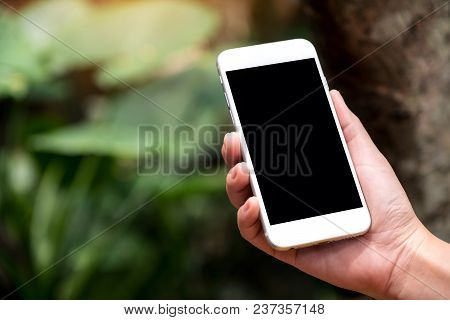 Mockup Image Of A Hand Holding White Smart Phone With Blank Black Desktop Screen In Outdoor With Blu