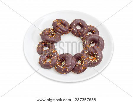 Cookies In A Shape Of Rings Glazed With Chocolate And Colorful Confectionery Sprinkles On A White Di