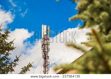 Antenna Cellular Network Against  Blue Sky And Surrounded By Trees