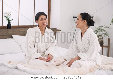 Happy Couple. Joyful Delighted Women Sitting In The Bed In The Spa Salon And Smiling