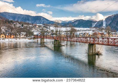 Slovak Village Of Nezbudska Lucka Near Strecno In The Winter, River The Vah With The Bridge In The F