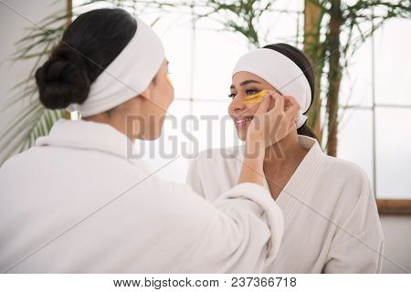 Staying Beautiful. Nice Delighted Positive Women Helping Each Other While Being In The Spa Salon
