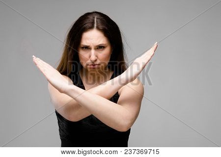 Half-length Portrait Of Angry Young Brunette Caucasian Girl In Black Dress On Gray Background Show S