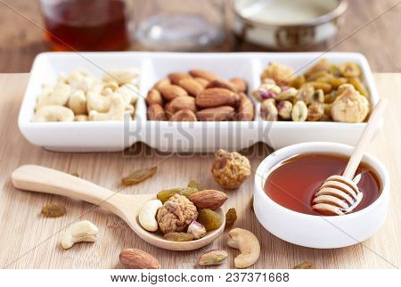 Dried Fruits And Variety Of Nuts Into A Dish And Bowl Of Honey On The Wooden Background, Such As Fig