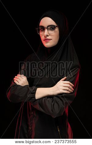 Attractive Confident Serious Muslim Arabian Woman Model Dressed In Black Hijab And Glasses Standing