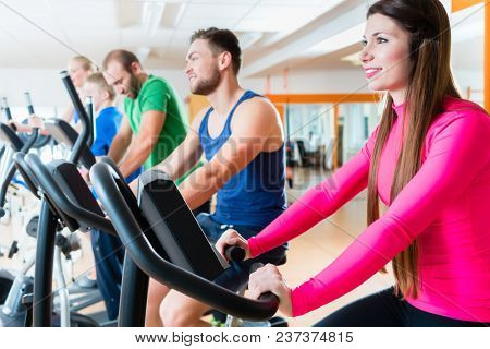 Male and female athletes doing spinning on home trainers in health club gym