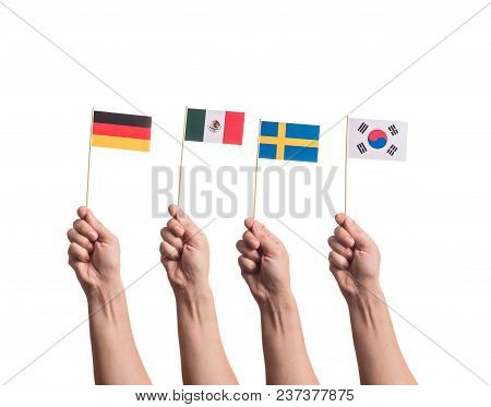 Little Paper National Flags In Hands Isolated On White Background. Flags Of National Football Teams