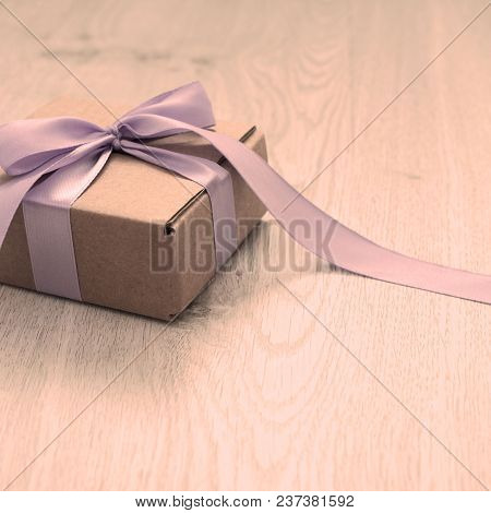 Gift Kraft Gift Box With Gift Satin Ribbon Bow. Wooden Vintage Background Toning. Copy Space For You