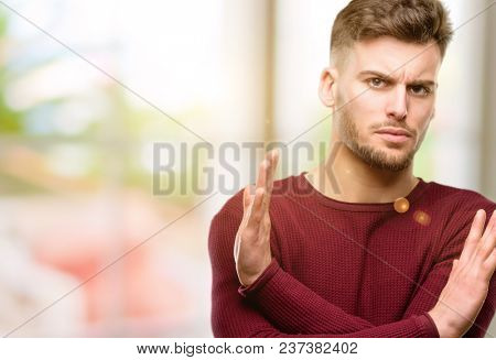 Handsome young man annoyed with bad attitude making stop sign crossing hands, saying no, expressing security, defense or restriction
