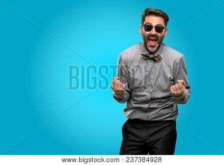 Middle age man, with beard and bow tie happy and excited celebrating victory expressing big success, power, energy and positive emotions. Celebrates new job joyful