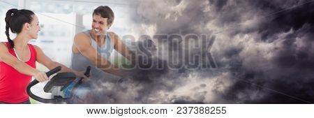 People smiling on gym bikes with stormy cloud transition