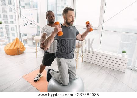 Medical Program. Handsome Strong Man Doing Special Exercises While Following Medical Program