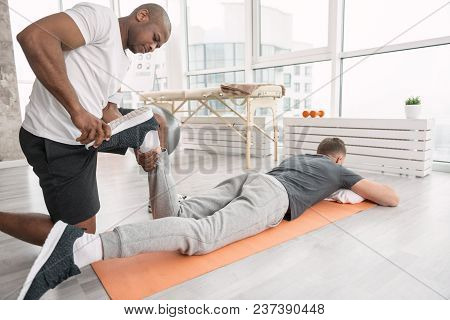 Physical Therapy. Serious Nice Man Looking At The Patients Leg While Being Responsible For The Physi