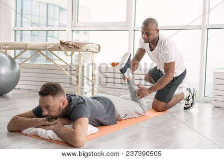 Physical Exercises. Skilled Male Trainer Standing Behind The Patient While Helping Him With Physical