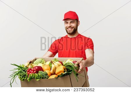 Delivery Concept: Handsome Caucasian Grocery Delivery Courier Man In Red Uniform With Grocery Box Wi