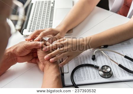 Female Doctor Holding Hands Of Senior Male Patient In Medical Room. Comforting. Stethoscope And Clip