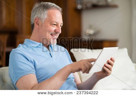 Portrait of a smiling senior man using a digital tablet in the living room of his home