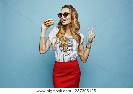 Beautiful And Fashionable Blonde Model Girl With Charming Smile, In Red Skirt White T-shirt And Sung