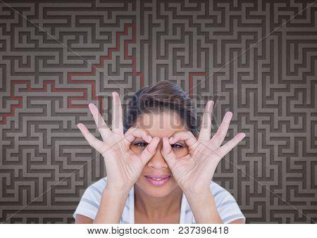 Woman doing binoculars symbols against maze background