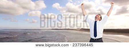 Business man celebrating on coastline
