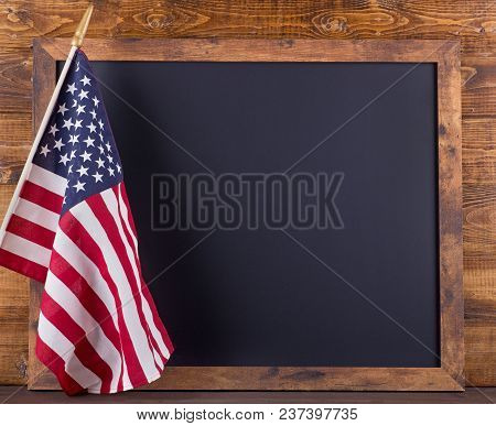 Blank Chalkboard For Copy Space With American Flag On A Rustic Wood Background