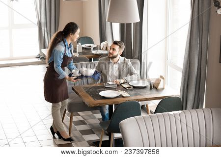 Smiling Content Beautiful Waitress Holding Tray With Tea And Giving Order To Customer Sitting At Tab