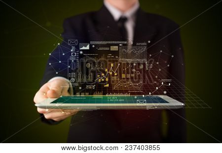 Businessman holding tablet with strategy and business related graphics