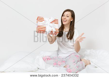 Young Brunette Woman Sitting In Bed With Red Striped Gift Box, White Sheet, Pillow, Wrapping In Blan