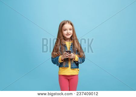 Happy Teen Girl Standing, Smiling With Mobile Phone Over Trendy Blue Studio Background. Beautiful Fe