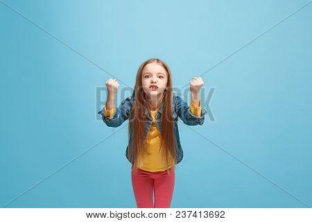 Angry Teen Girl Standing On Trendy Blue Studio Background. Female Half-length Portrait. Human Emotio