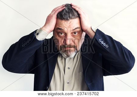 Bearded Man Holds His Head With Both Hands. Problems. Lack Of Time. Do Not Go Business. A Lot Of Wor