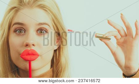 Young Adult Woman Applying Lipstick Or Lip Gloss, Getting Her Make Up Done Holding Fake Lips On Stic