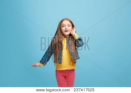 The Happy Teen Girl Standing And Listening On Trendy Blue Studio Background. Beautiful Female Half-l