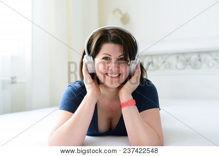 A Woman Listens To Music On Headphones And Lies On The Bed.