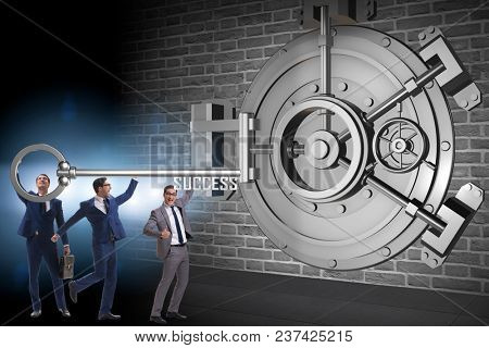 Businessman with key near bank vault door