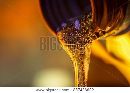 Liquid Stream Of Motor Oil Flows From The Neck Of The Bottle Close-up