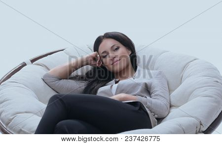 young woman sitting in a comfortable soft big armchair