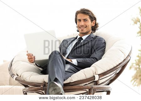 confident businessman working with laptop sitting in comfortable armchair