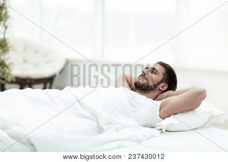 tired man resting on a comfortable bed