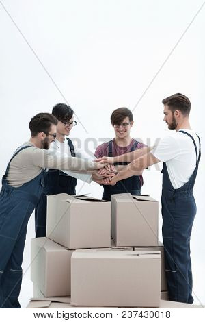 Cheerful movers leaning on stack of boxes isolated on white back