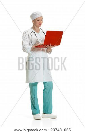 Beautiful Young Woman In White Coat Posing At Studio With Red Laptop. Full Length Shot Isolated On W