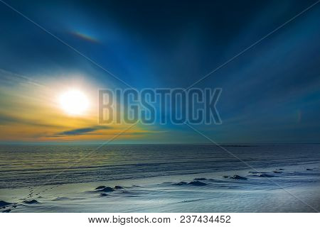 The Setting Winter Sun And Solar Halo Over The Frozen River. Western Siberia, Novosibirsk Region, Ob