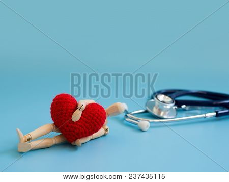 Wooden Puppet Hugging Red Heart And Fall Down On The Floor In Front Stethoscope. Copy Space For Text