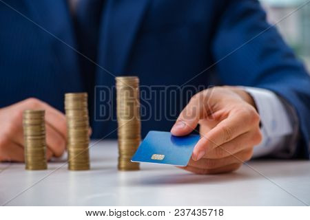 Businessman with stacks of coins in the office