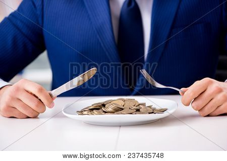 Funny businessman eating gold coins in office