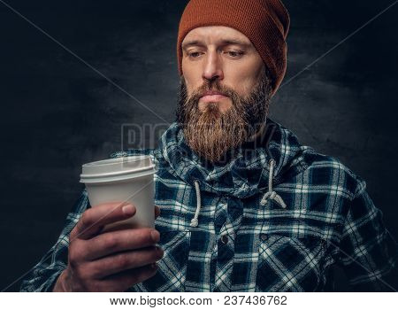 Brutal Bearded Male Dressed In A Hat And Fleece Shirt, Drinks Coffee From A Paper Glass.