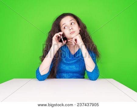 Suspicious Customer Having A Telephone Conversation And Looking At The Side Sitting At A Table On A